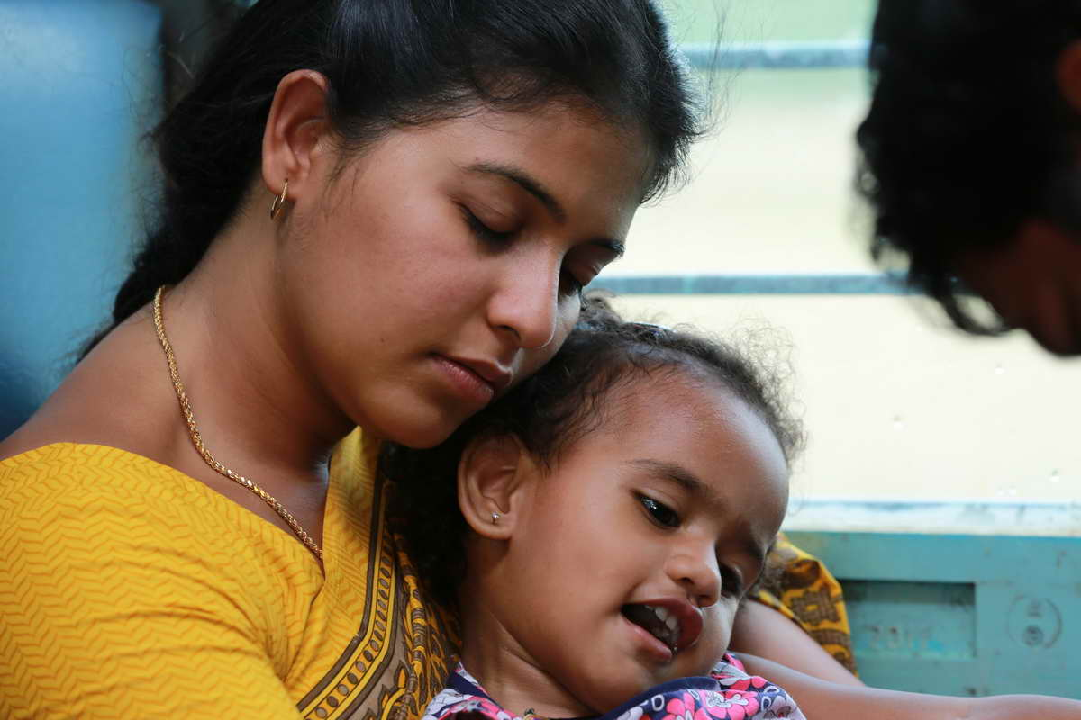 A brown woman in a yellow sari has her eyes closed as she rests her head atop that of a young, brown girl.